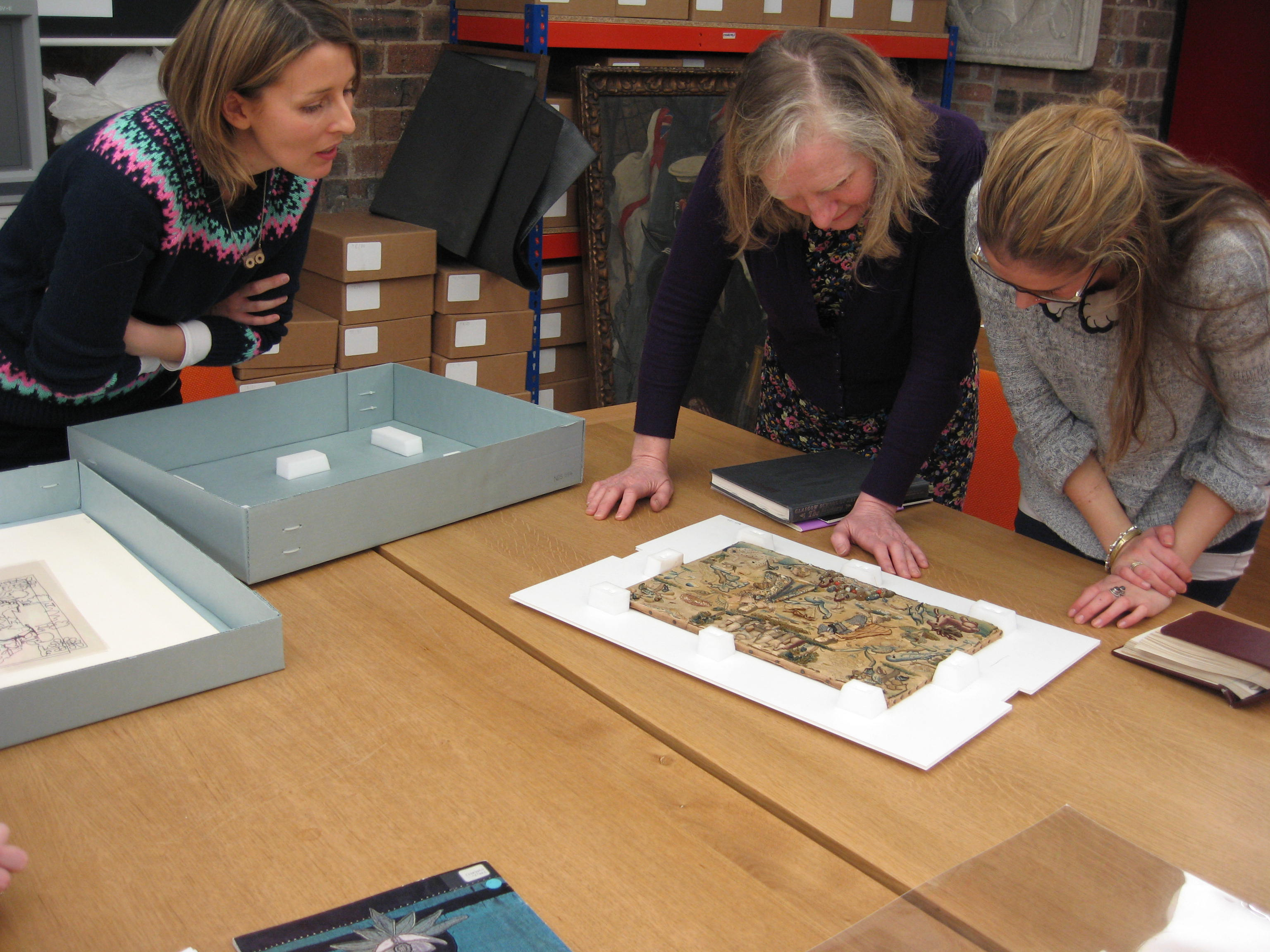 GSA's Archivist Susannah shows ECA researchers Lindy and Lucie some items from our Needlework Development Scheme textile collection.