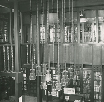 Photograph of the library on the first floor of the Mackintosh Building, taken from the gallery and showing ceiling lights in detail. (Archive Reference: GSAA/P/7/190)