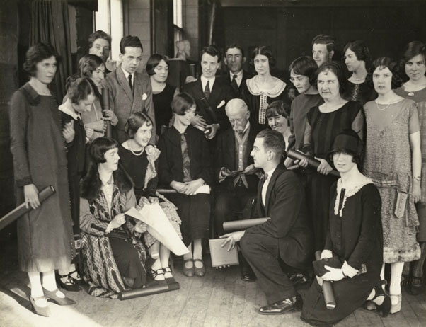 Glasgow School of Art students gathered around Patrick Smith Dunn, Governor of School, featuring Charles Cameron Baillie, Duncan Shanks (Sen), Isabel Goudie, Margaret Nairn, Nonie McCrone, Alexander McPherson, Mary Armour, Isa Cleland, Robert Milne, Betsy. 1923-1924. GSA Archives Collections. http://www.gsaarchives.net/archon/index.php?p=digitallibrary/digitalcontent&id=2013